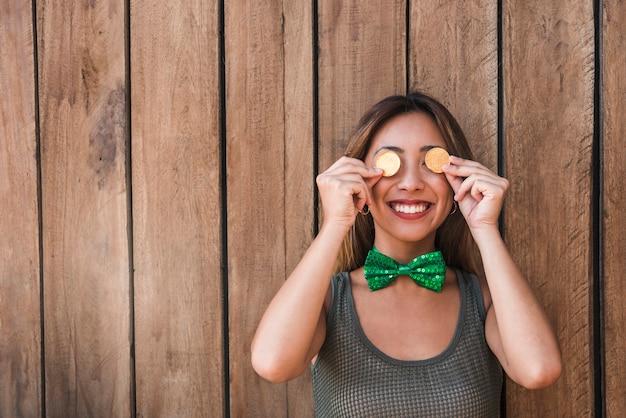 Mujer sonriente sosteniendo monedas de oro cerca de los ojos