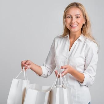 Mujer sonriente sosteniendo un montón de bolsas de la compra.
