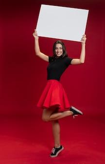 Mujer sonriente sosteniendo una pancarta vacía