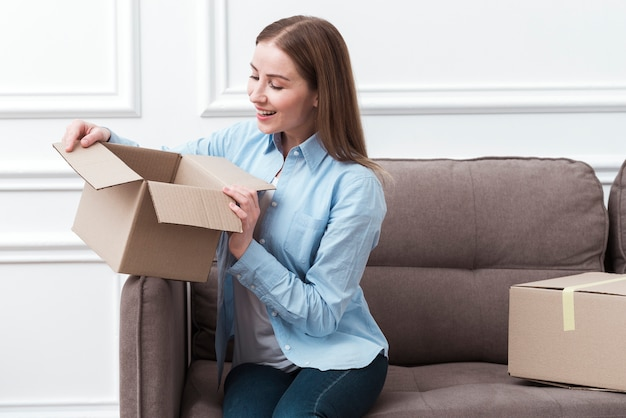Mujer sonriente sosteniendo un paquete en el interior y sentado en el sofá