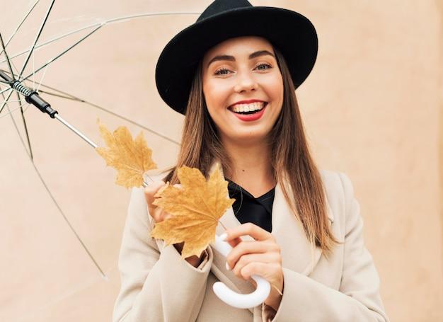 Mujer sonriente sosteniendo un paraguas transparente y hojas