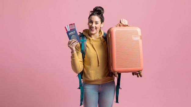 Mujer sonriente sosteniendo pasaporte de salud y equipaje