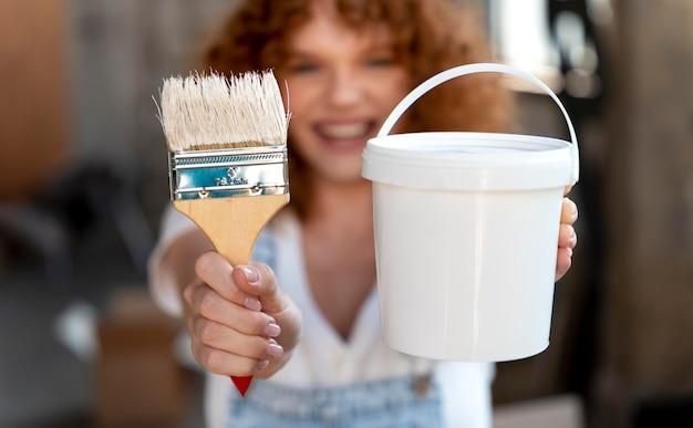 Mujer sonriente sosteniendo un pincel y un cubo para la nueva decoración del hogar