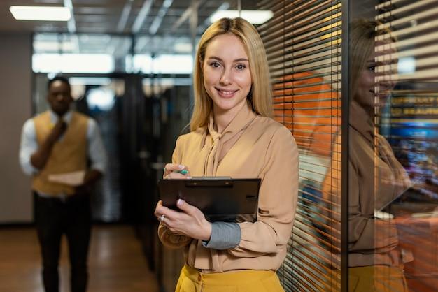 Mujer sonriente sosteniendo portapapeles en el lugar de trabajo
