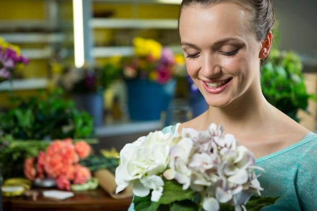 Mujer sonriente sosteniendo un ramo de flores