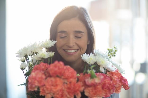 Mujer sonriente sosteniendo un ramo con los ojos cerrados