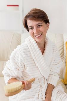 Mujer sonriente sosteniendo un spa de cepillo en el concepto de casa