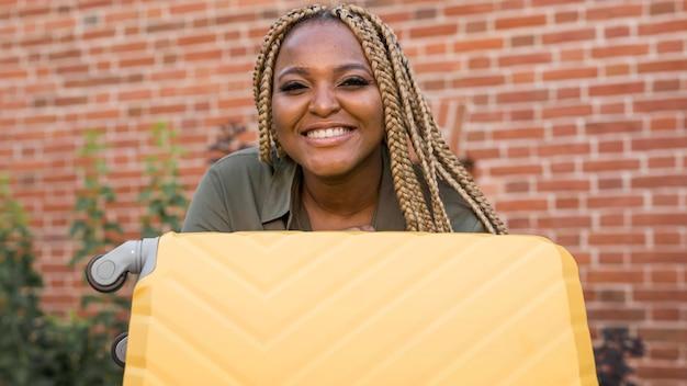 Mujer sonriente sosteniendo su equipaje amarillo