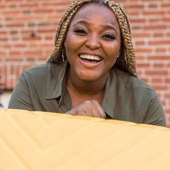 Mujer sonriente sosteniendo su equipaje