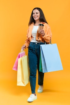 Mujer sonriente sosteniendo una taza de café y un montón de bolsas de la compra.