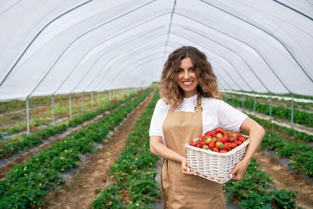 Mujer sonriente sostiene canasta con fresas
