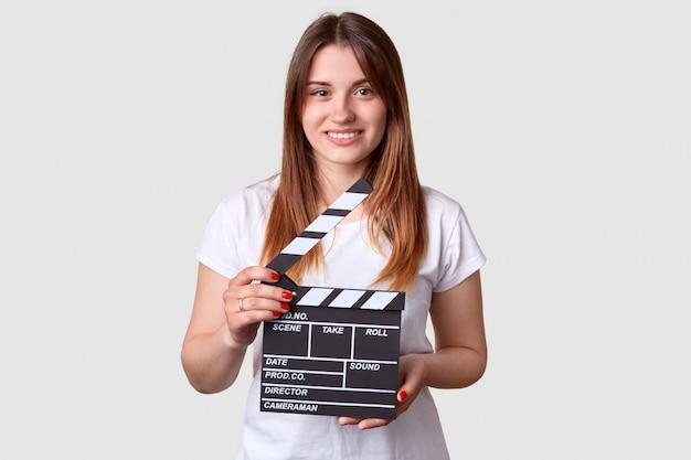Mujer sonriente con una suave sonrisa, sostiene el tablero de la chapaleta de la película