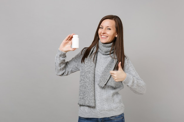 Mujer sonriente en suéter gris, bufanda mostrando el pulgar hacia arriba, mantenga tabletas de medicación, píldoras de aspirina en botella aislada sobre fondo gris. estilo de vida saludable, tratamiento de enfermedades enfermas, concepto de estación fría.
