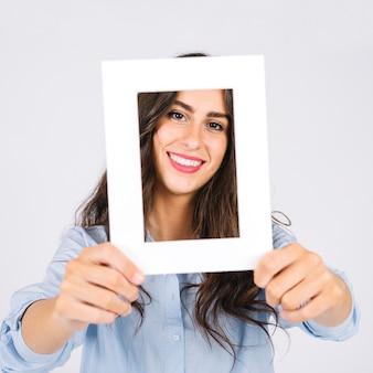 Mujer sonriente sujetando marco enfrente de cara