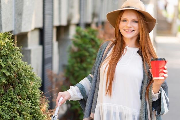 Mujer sonriente con taza al aire libre