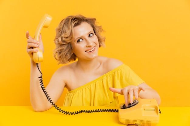 Mujer sonriente con teléfono antiguo