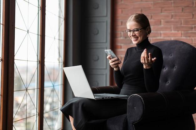 Mujer sonriente con teléfono y computadora portátil