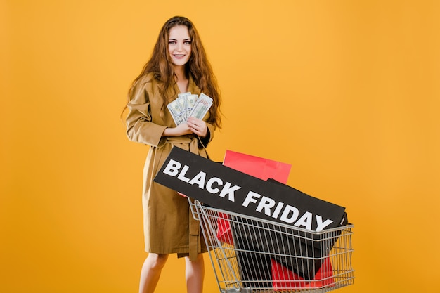 Mujer sonriente tiene dinero y signo de viernes negro con coloridas bolsas de compras en carro aislado sobre amarillo