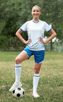 Mujer sonriente de tiro completo con balón de fútbol