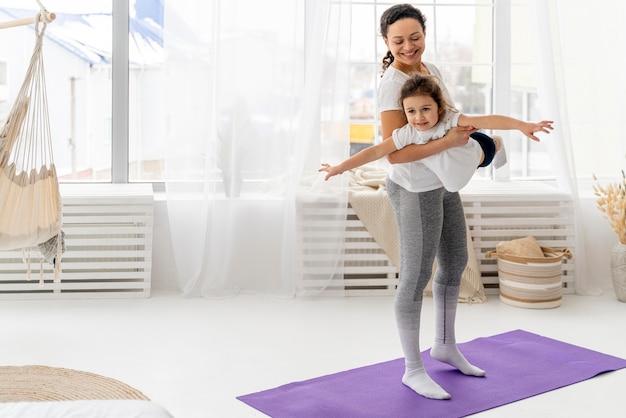 Mujer sonriente de tiro completo entrenando con niño
