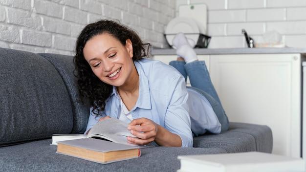 Mujer sonriente de tiro completo leyendo en el sofá