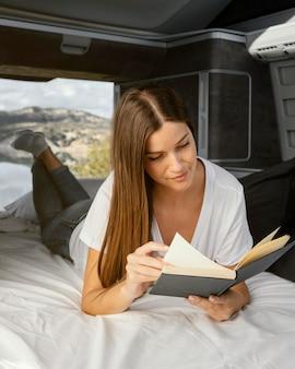 Mujer sonriente de tiro completo leyendo