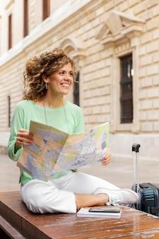 Mujer sonriente de tiro completo con mapa