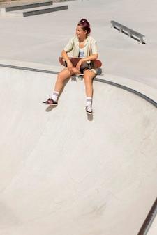Mujer sonriente de tiro completo con patineta fuera