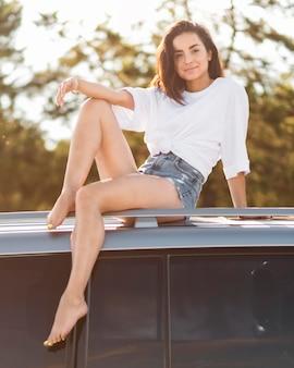 Mujer sonriente de tiro completo posando en coche