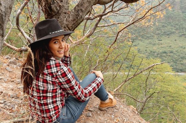 Mujer sonriente de tiro completo sentado al aire libre