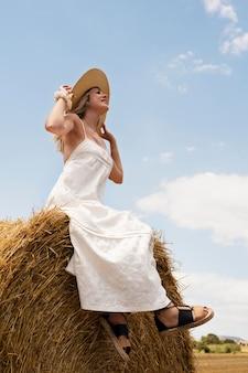 Mujer sonriente de tiro completo sentado en el heno