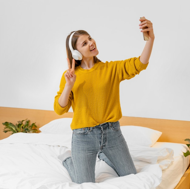 Mujer sonriente de tiro completo tomando selfie