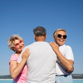 Mujer sonriente de tiro medio abrazando al hombre