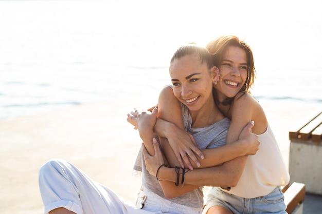 Mujer sonriente de tiro medio abrazando a su amiga