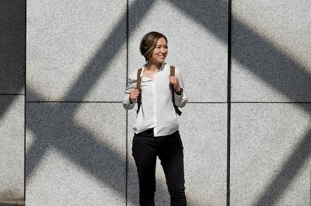 Mujer sonriente de tiro medio con auriculares