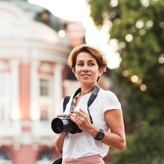 Mujer sonriente de tiro medio con cámara