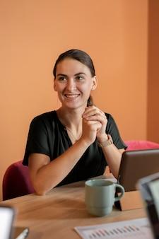 Mujer sonriente de tiro medio en el escritorio