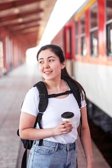 Mujer sonriente de tiro medio en la estación de tren