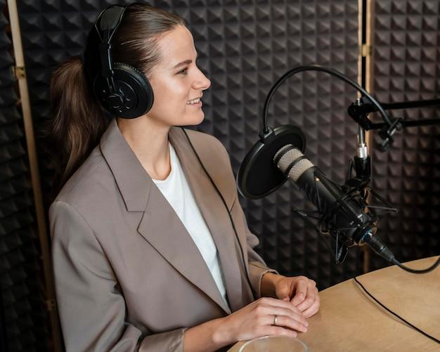 Mujer sonriente de tiro medio hablando por radio