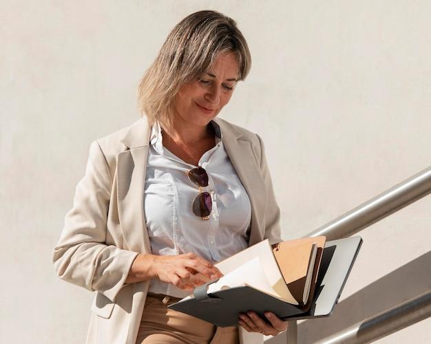 Mujer sonriente de tiro medio leyendo documentos