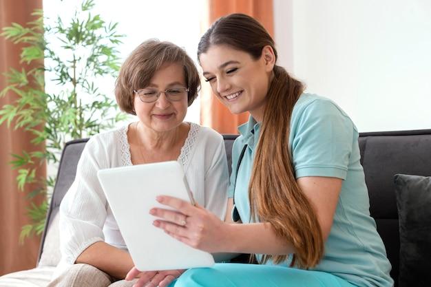 Mujer sonriente de tiro medio mirando tablet