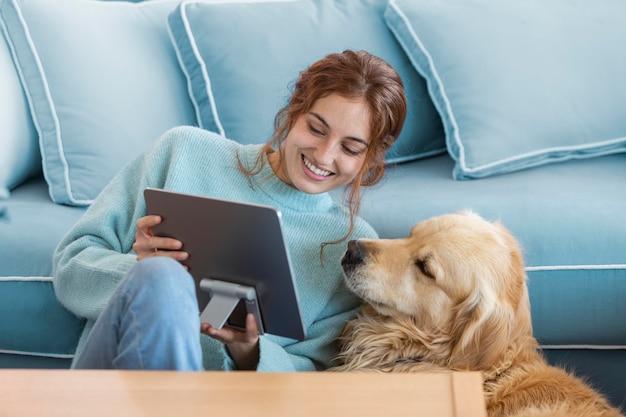 Mujer sonriente de tiro medio y perro con tableta