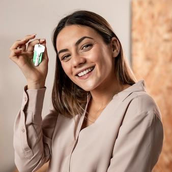 Mujer sonriente de tiro medio sosteniendo llaves