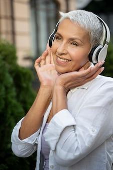 Mujer sonriente de tiro medio usando audífonos