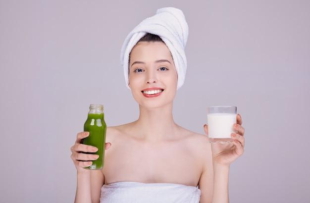 Mujer sonriente en una toalla sostiene un vaso de leche y una botella con batido.