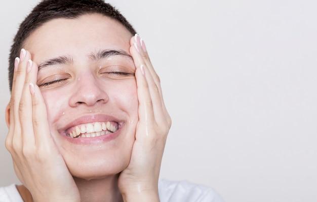 Mujer sonriente tocando la piel de la cara suave