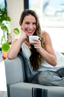 Mujer sonriente, tomando café, sentada en su sofá