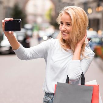 Mujer sonriente tomando selfie al aire libre con bolsas de la compra.