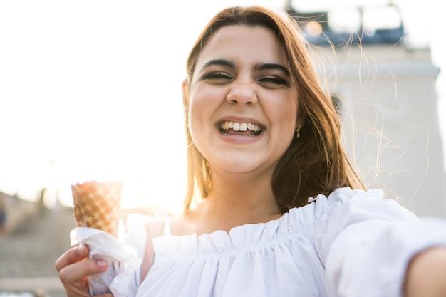 Mujer sonriente tomando un selfie mientras come un helado con una puesta de sol en el fondo