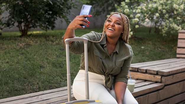 Mujer sonriente tomando un selfie mientras viaja